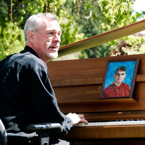 Steve Schalchlin playing John Lennon's piano. Bill Clayton watches on from the photograph. May 8, 2007, in Olympia, WA. Photo by Caroline True.
